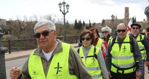 Los primeros peregrinos atraviesan el puente del Ebro en la primera etapa de la javierada que les llevará a la ermita de la Virgen del Yugo