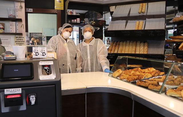 Dependientas de un despacho de pan con el uiforme de seguridad por la crisis del coronavirus